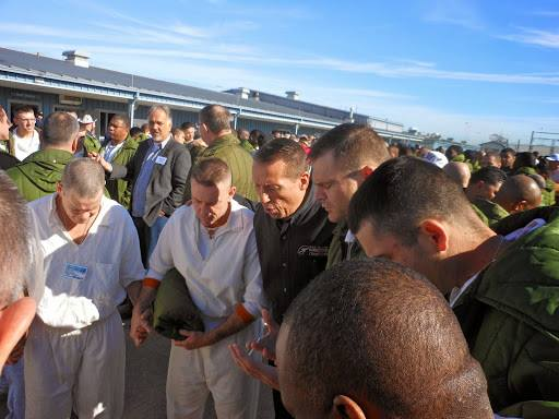 men praying together outside in prison yard